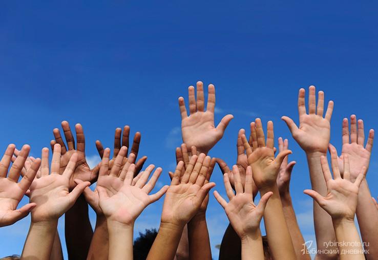 Волонтерские руки на синем небе