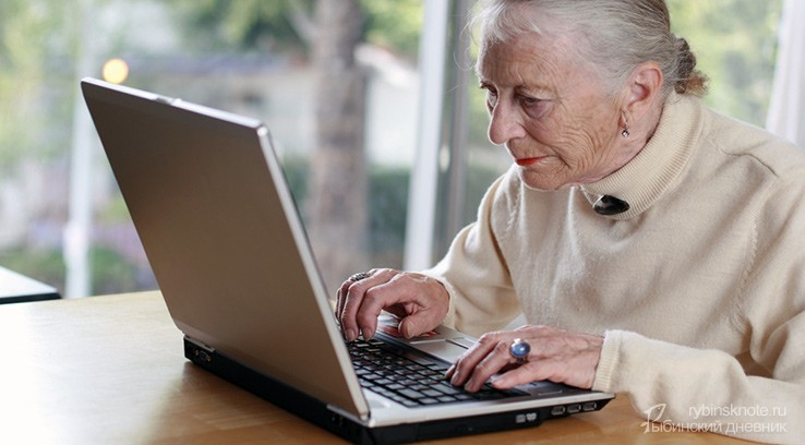 Бабушка сидит за ноутбуком