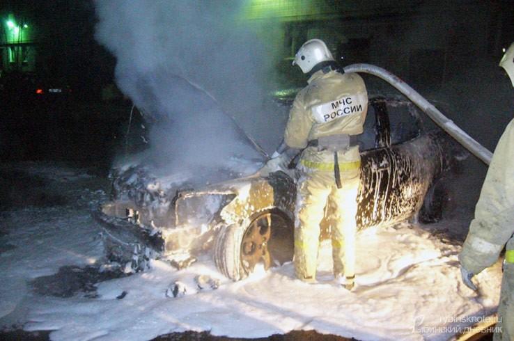 Пожарный рядом с потушенной машиной в пене