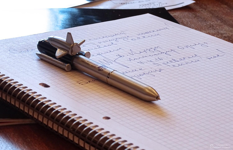 Ручка в форме ракеты на фоне автографа Корзуна