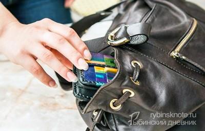 Женская рука крадет из сумки кошелек